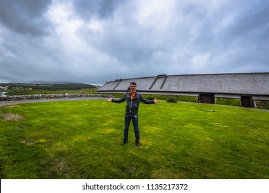 Borg - June 15, 2018: Traveler at the Replica of the Longhouse in the Lofotr Viking Museum at the town of Borg in the Lofoten Islands, Norway