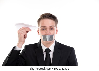 Boring businessman with tape on his mouth hold a paper plane