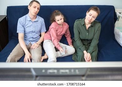 langweilige kaukasische Familie, die auf einem Sofa sitzt, um Zeit zusammen mit Fernsehen zu verbringen, Leute, die zu Hause bleiben