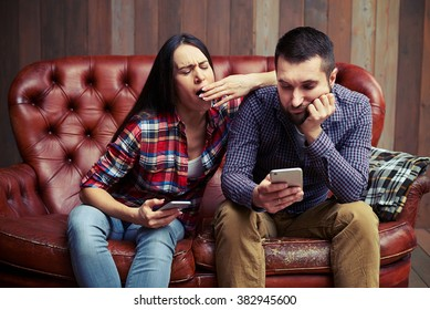 boring couple sitting on sofa and looking at smartphone