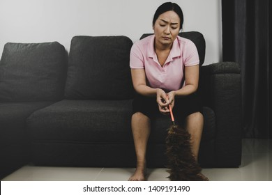Boring home concept : Job of a housewife holding a hair brush is to clean everything inside the house until sometimes feeling bored.