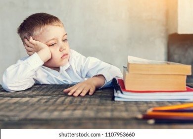 Boring homework. Tired little sad pupil looking at his big books and copybooks while sitting at the table