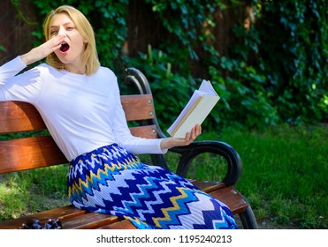 Boring literature. Woman yawning blonde take break relaxing in garden reading book. Girl sit bench relaxing with book, green nature background. Lady student read boring literature outdoors.