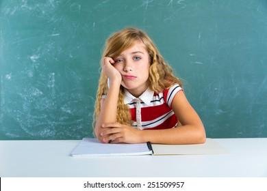 Boring sad expression student schoolgirl on classroom desk at school green chalk board