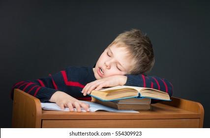 Boring School Studies. So Tired of Homework. Cute kid sleeping on old books. Education.