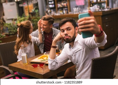 Boring selfie. Sad lonely young man sitting at the table with friends and feeling bored while taking selfies
