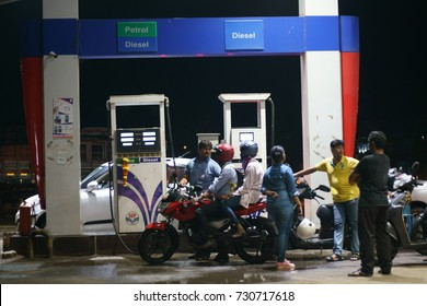BORIVALI HIGHWAY, MUMBAI, MAHARASHTRA, INDIA - OCTOBER 8, 2017: A line of people are gathered to fill petrol/ diesel in their vehicles at a local petrol station on the BORIVALI HIGHWAY.