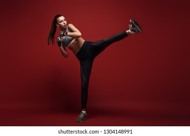 Born to win. Attractive sportswoman doing kickboxing exercises isolated over red background