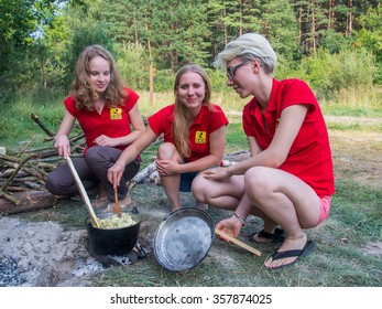 Borne Sulinowo, Poland - August 23, 2015: Three young pretty girls cook a meal in a pot at the picnic