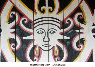 BORNEO, INDONESIA - 07 JULY 2011: Traditional Dayak tribal culture. Traditional graphics on the wall in front of Dayak house - long house. East Kalimantan, Borneo