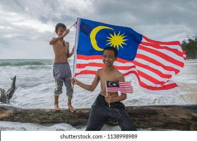 Borneo, Malaysia - 14th July 2018 : Bajau (Sea Gypsies) kids holding Malaysian flag on beach. Malaysian celebrates Independence Day on 31st August every year.