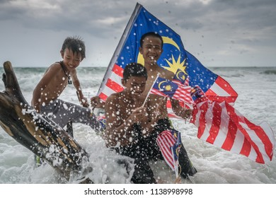 Borneo, Malaysia - 14th July 2018 : ajau Laut kids holding Malaysian flag on a beach near Kudat. Malaysian celebrates Independence Day on 31st August yearly