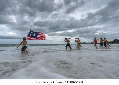 Borneo, Malaysia - 14th July 2018 : Bajau (Sea Gypsies) kids running on beach holding Malayysian flag