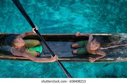 Borneo, Sabah - April 2013 - Two sea gypsies brother paddling their small boat on a emerald sea in Mabul Island, Borneo, Sabah, Malaysia.