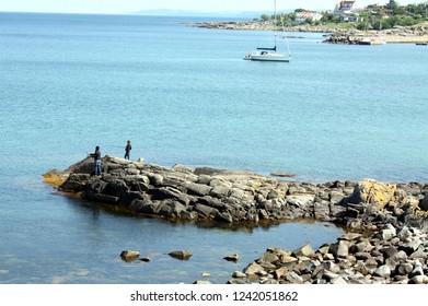 Bornholm. June-09-2012. Children fishing on the rocks of the Danish island Bornholm