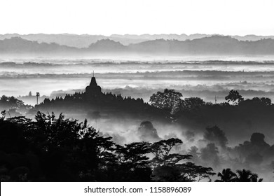 Borobudur temple silhouette in black and white format with foggy layer landscape background. Taken in early morning before sunrise