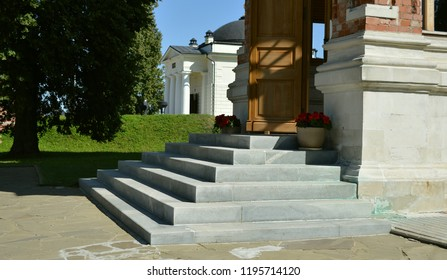 The Borodino Convent of Our Savior (Savior-Borodino Monastery) on the Borodino field (Russia). The entrance porch doorstep with grey stone stairs, a wooden door and two flower pots with red flowers