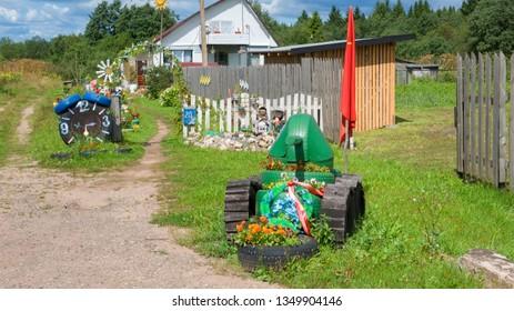 Borovichi, Russia - August 8, 2018: Figures made from old car wheels. Landscape design in front of the farmhouse.  Novgorod region, Borovichi, Russia