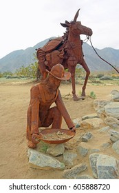 Borrego Springs, California (Feb 21, 2015) - Public Art - A closeup view of metal sculptures of a prospector panning for gold and his pack mule in the background laden with his supplies