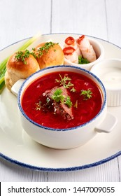 borsch with pampushkas, lard and onion at white table top. borsch is traditional ukrainian cuisine red soup with beet, potato, meat, carrot, cabbage and garlic. vertical shot with copy space