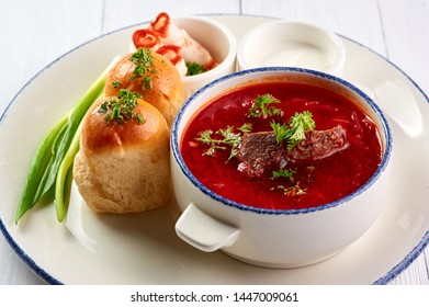 borsch with pampushkas, lard and onion at white table top. borsch is traditional ukrainian cuisine red soup with beet, potato, meat, carrot, cabbage and garlic
