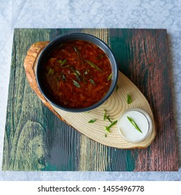Borsch with sour cream in a plate on a wooden board
