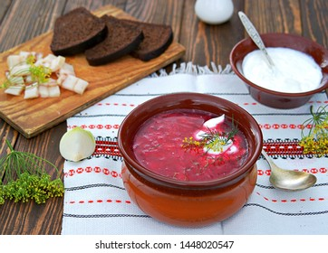 Borscht, hot soup with beets, cabbage and carrots in a clay bowl. Served with sour cream, rye bread and bacon.