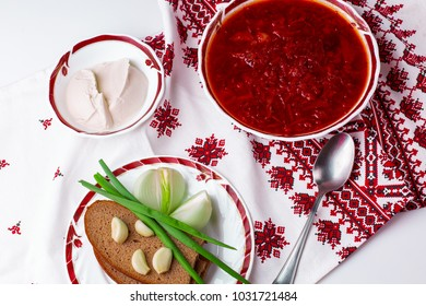 Borscht on a traditional towel with bread greens and sour cream on a table