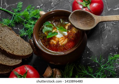 borscht with sour cream in a clay pot with black bread garlic tomatoes and greens