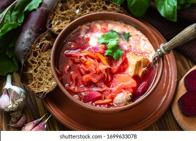 Borscht Ukrainian traditional dish cuisine photo for menu, Russian borscht food background. Bowl of red beet root homemade soup with vegetables pepper cabbage potatoes tomato sauce sour cream top view