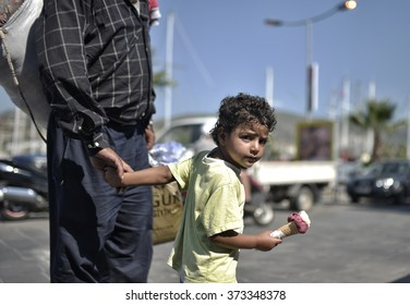 BORUM,TURKEY, 5 SEPTEMBER 2015, Syrian refugees child eating ice cream holding her father hand in Bodrum while waiting district for to switch the Greece Kos island.