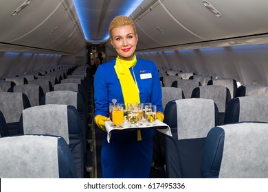 Boryspil, Ukraine - APRIL 06, 2017: Flight attendant with tray with drinks. Cabin crew member serving. Airplane interior.
