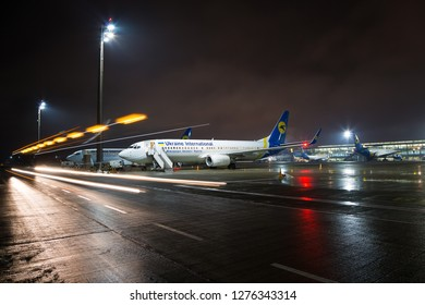 BORYSPIL, UKRAINE - DECEMBER 19, 2018:  Boryspil International airport. Ukraine International Airlines FlyUIA aircraft Boeing 737 waiting for passengers boarding at the airport.  Night airport.