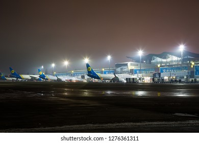 BORYSPIL, UKRAINE - DECEMBER 19, 2018:  Boryspil International airport. Ukraine International Airlines FlyUIA aircrafts waiting for passengers boarding at the airport.  Night airport.