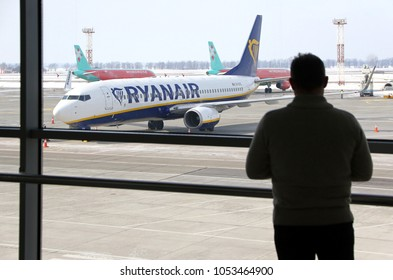 BORYSPIL, UKRAINE - MARCH 23, 2018: Man watch through the window to the first Ryanair plane landed at Kyiv Boryspil airport. On this day Ryanair signs the agreement to enter Ukraine's market
