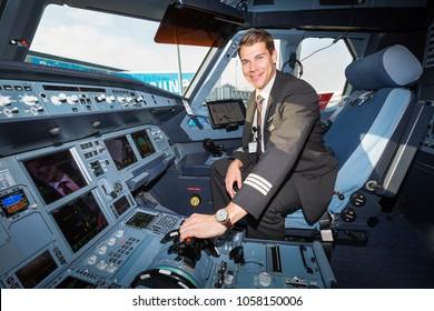 BORYSPIL, UKRAINE - MARCH 26, 2018:  Airline pilot posing in the cockpit. Airbus A320 cockpit. Pilot prepairing for the flight.