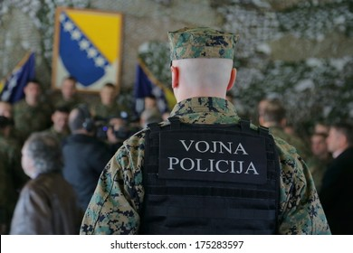 Bosnian Military officer protects a group of people