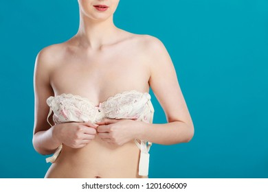 Bosom concept. Slim attractive naked woman dressing up or putting on her white lacy bra on blue