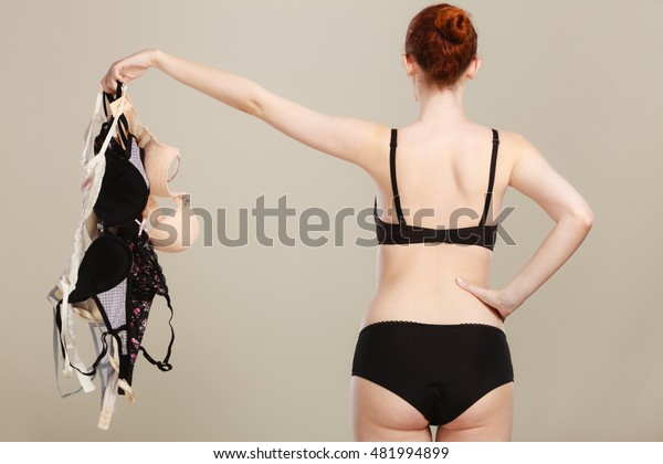Bosom concept. Slim attractive red hair woman wearing black underwear holding many bras in hand, choosing witch bra to wear, rear view