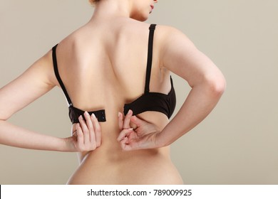 Bosom concept. Slim attractive woman taking off or putting on her black bra rear view