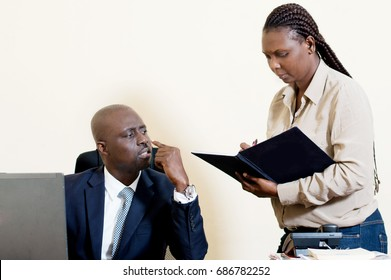 The boss asks his secretary to show him what she has noted.