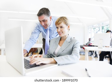 A Boss Assisting his Employee in Front of the Laptop