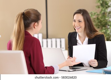 Boss attending to an employee during a job interview in a desktop at office