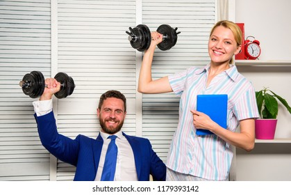 Boss businessman and office manager raise hand with dumbbells. Strong business team. Healthy habits in office. Man and woman raise heavy dumbbells. Strong powerful business strategy. Good job concept.