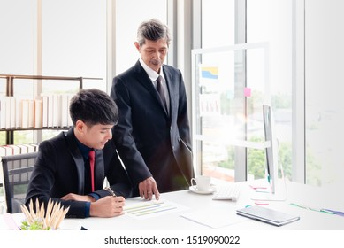 The boss businessman stood and checking the point to the report. He is discussing with the young staff on the desk in his office room.