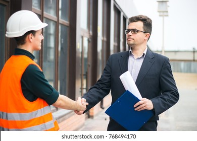 boss or Chief handshaking with workers engineers and giving salary in an envelope. Good job. Business modern background.