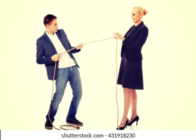 Boss concept-woman holding rope in two fingers, man pulling a rope and can't win