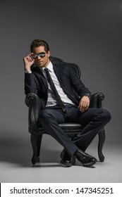 I am a boss. Confident young businessmen in sunglasses sitting on the vintage chair while isolated on grey