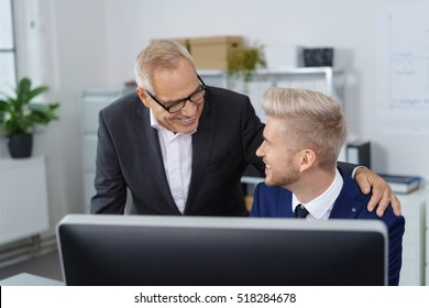 Boss congratulating young adult worker seated behind computer monitor in small office