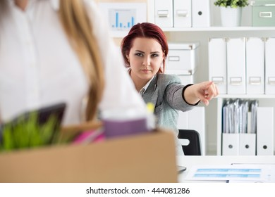 Boss dismissing an employee. Dejected fired office worker carrying a box full of belongings. Getting fired concept.